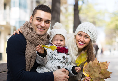 thirties portrait: Autumn portrait of happy young cheerful parents with child. Shallow focus
