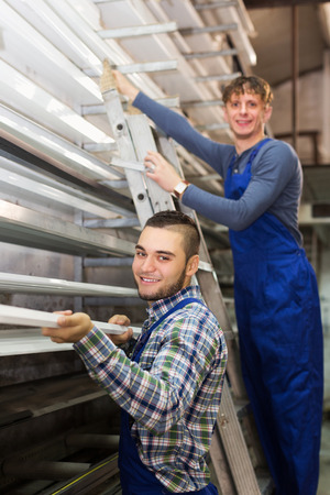 toolroom: Smiling production workmen in uniform with different PVC window profiles indoor