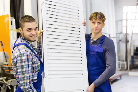 workers in coverall with  PVC window with shutter at plant Stock Photo