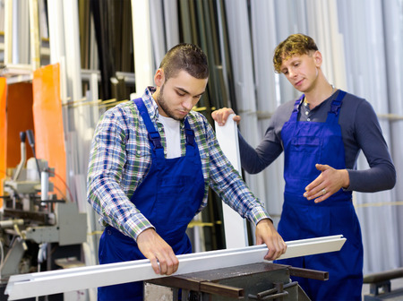 toolroom: Couple of workmen cutting PVC window profiles on a lathe Stock Photo