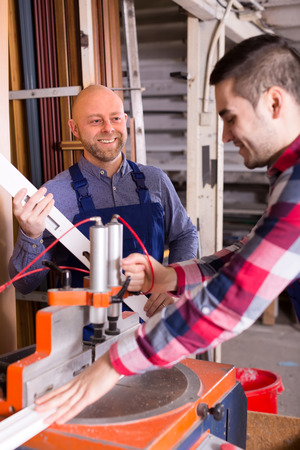 toolroom: Men in workwear working on a lathe in a workshop
