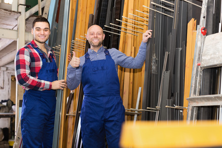 toolroom: Two smiling workers posing in PVC shop Stock Photo