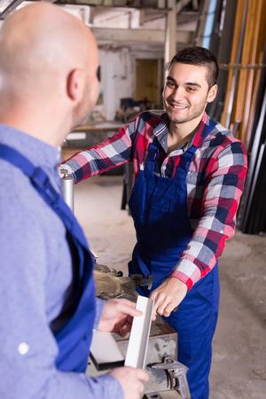 skilled operator: Professional workmen cutting pvc profiles on a lathe Stock Photo