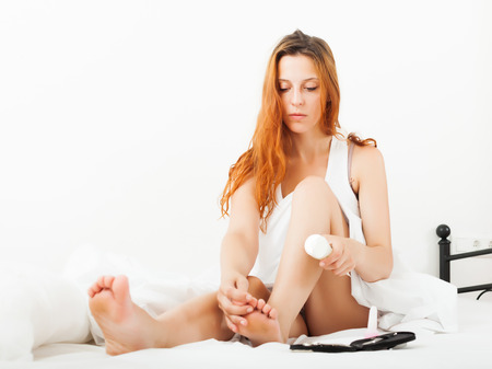 woman caring for feet with cosmetic cream in bed