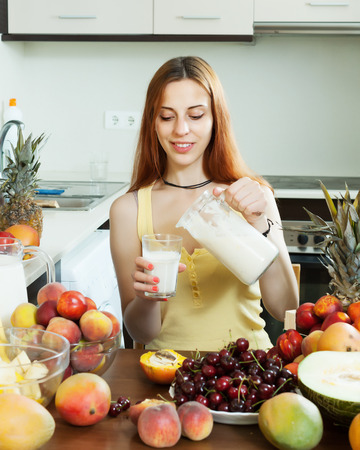 woman drinking milk: cheerful woman  drinking milk cocktail with fruits at home Stock Photo
