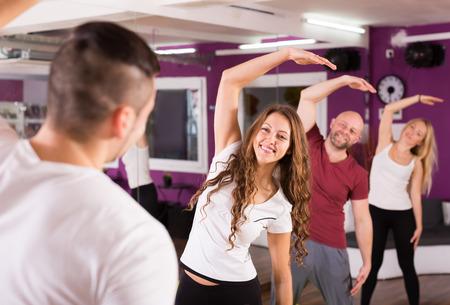 estudiantes adultos: Grupo de personas de los hombres y las mujeres entrar en calor en un gimnasio Foto de archivo