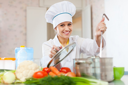 Professional cook in white hat works in the kitchen