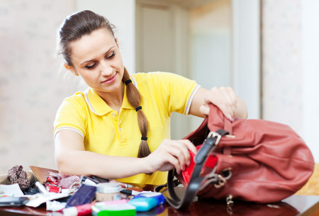 ransack: Upset inconsiderate woman lost something and finding in handbag Stock Photo