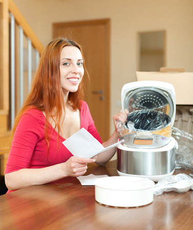 Happy young  housewife unpacking new multicooker in home in living room photo