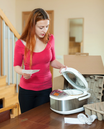 slow cooker: Young woman with electric slow cooker in kitchen at home