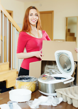 Happy young woman unpacking new multicooker in home interior photo