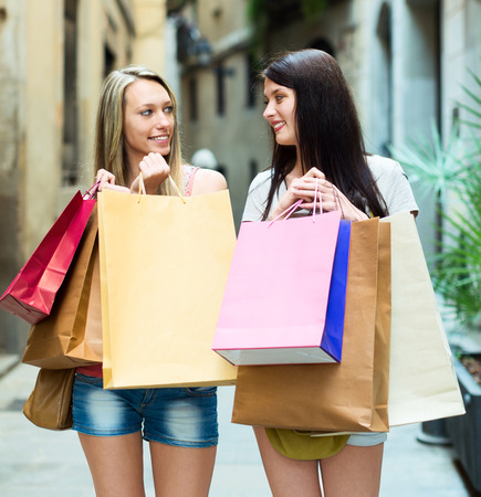rejoicing: Two happy girls rejoicing purchases in European city