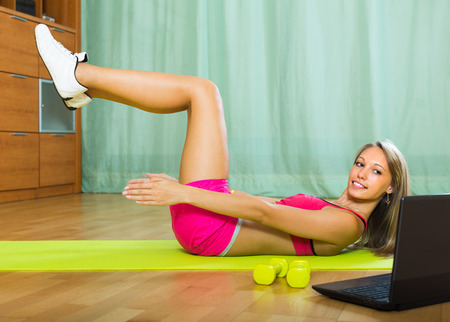Active smiling young woman working out with notebook in gym Stock Photo