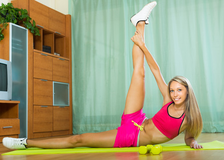 house trained: Smiling sporty young woman training with dumbbells at home