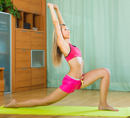 house trained: Happy slender young woman doing yoga at home