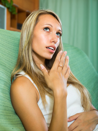 ennui: Unpleased young woman yawning on couch in living room