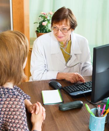 consulta m�dica: Mujer que tiene consulta m�dica en el consultorio del doctor mayor
