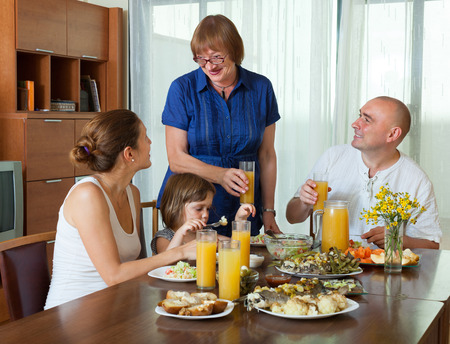 three generations: Portrait of happy three generations family posing together over healthy table at home interior