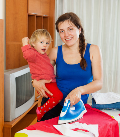 the iron lady: Young housewife ironing clothes on the ironing board with baby