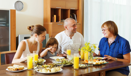 celebratory: multigeneration family  eating fish with vegetables at home together