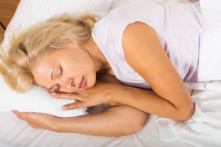 Blonde middle-aged woman sleeping in bed at home photo