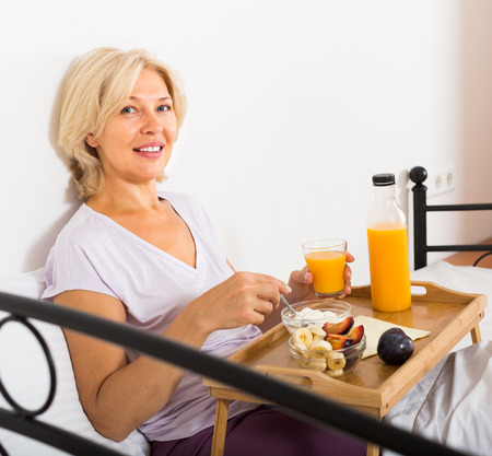 Smiling mature woman enjoying healthy breakfast in bed photo