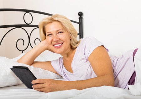 Happy mature woman with eBook laying in  bed photo