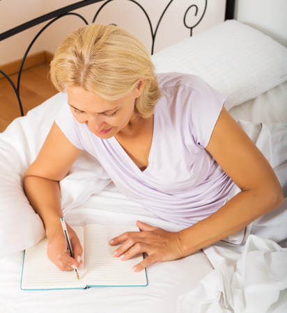Middle-aged woman writing in notebook on white sheet in bed at home photo