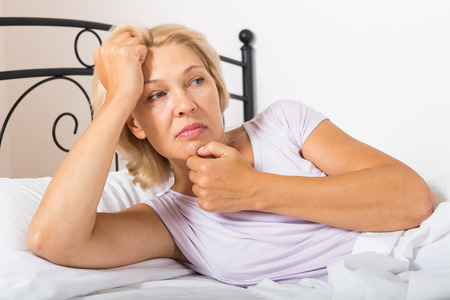 ennui: unhappy mature woman laying in bed