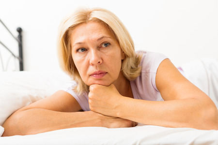 ennui: unhappy mature female with head reclined upon hands in bed