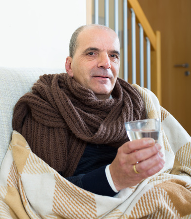 linctus: Mature male with scarf, blanket and dissolving medicine in glass at home Stock Photo