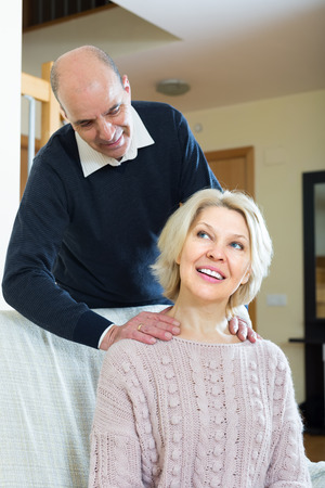 Portrait of senior man giving tired wife a back massage photo