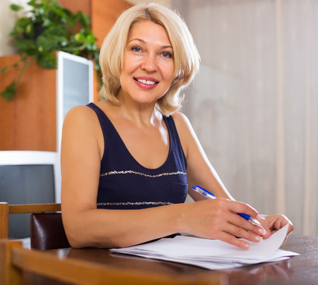 fifty something: Portrait of mature positive woman with financial documents in office interior Stock Photo