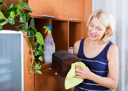 cleanser: Mature housewife cleaning casket with cleanser and rag at home