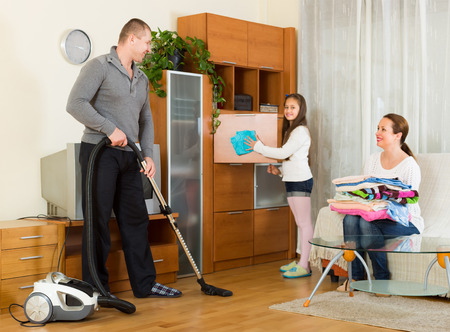 Happy smiling preschooler girl helping parents to clean at living room. Focus on man photo