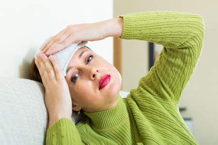 Tired of problems woman sitting on sofa with intense headache photo