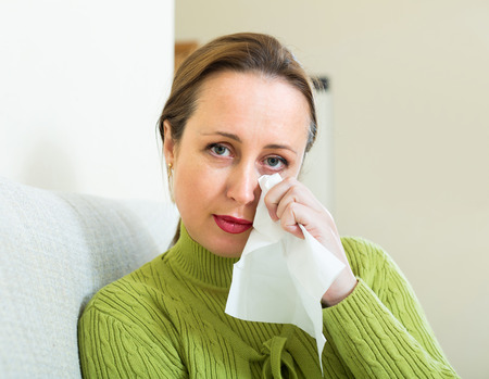 heartbreak issues: Sad and lonely woman sitting on couch at home Stock Photo
