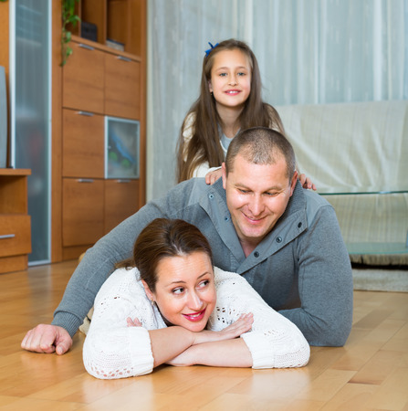 Happy smiling family of three on the floor at home. Focus on woman photo