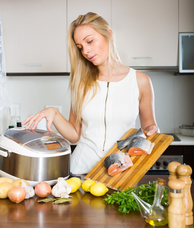 Young woman cooking salmon with new electric multicooker at home photo