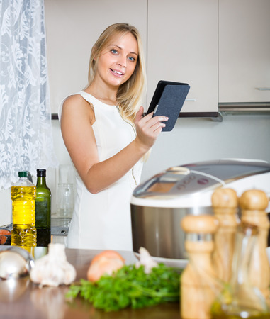 ereader: Long-haired girl reading ereader while with new electric multicooker doing food at home Stock Photo
