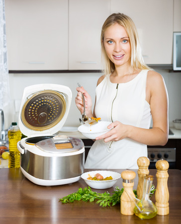 Young girl cooking fish soup with salmon and  electric multicooker photo