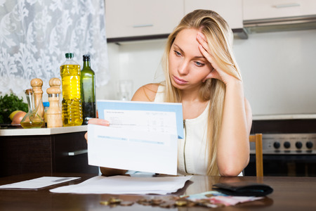 penury: Sad   woman thinking about the financial problems  at home Stock Photo