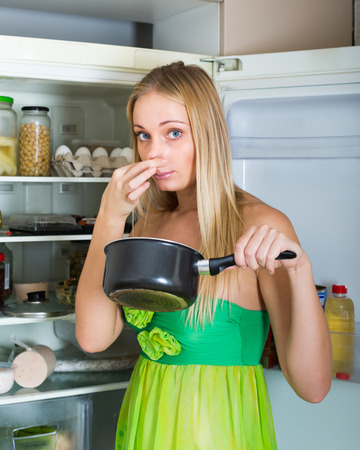 addle: Blonde woman holding her nose because of bad smell near fridge at home