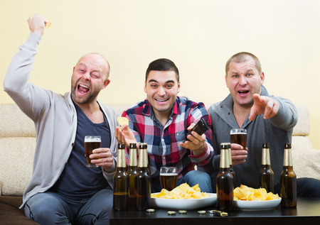 fan: Three male sport fans watching hockey game heatedly in livingroom Stock Photo