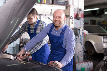 smile face: Portrait of two successful smiling car mechanics at workshop
