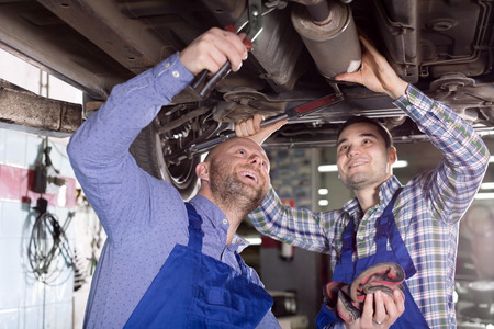 journeyman: Happy two male workers in overalls working in the garage. Focus on the left man