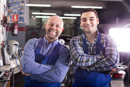 two car garage: Portrait of two happy professional car mechanics at garage