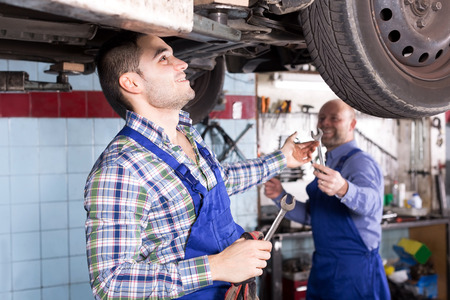 specialists: Young male mounting specialists working at auto repair shop.