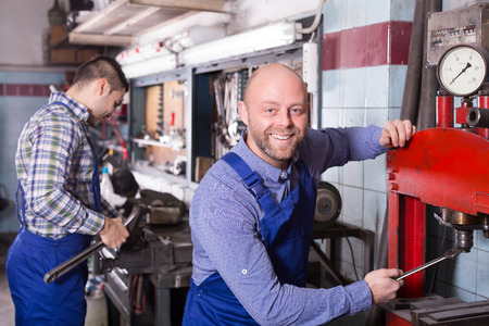 toiling: Two workmen toiling in the locksmiths workshop and smiling