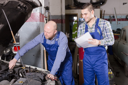 work workman: Workman calculating the price of work at auto repair shop Stock Photo